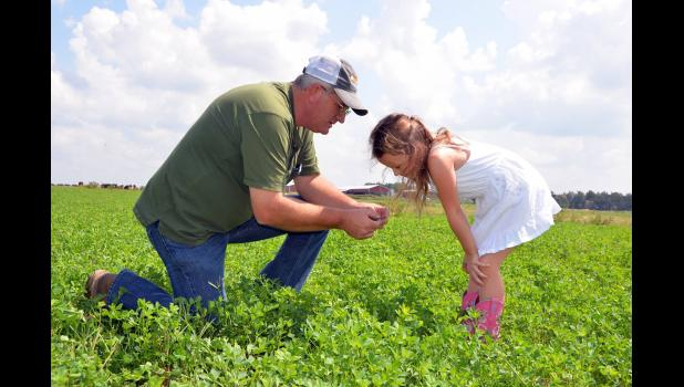 Charles Fletcher of Edgewood Dairy and Creamery tells his granddaughter about the value of good grazing forage. Photo courtesy of Edgewood Dairy