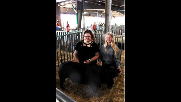 From left, Ella Johnson,17, and Maci Johnson, 15, with their pig Rufus.
